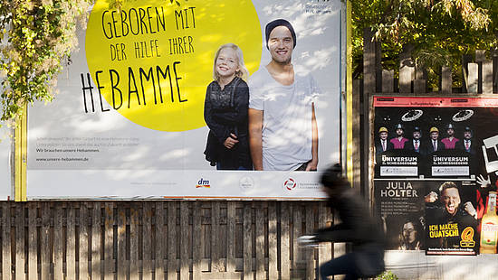 "big poster showing two kids ""born with the help of their midwife"" at the countryside"